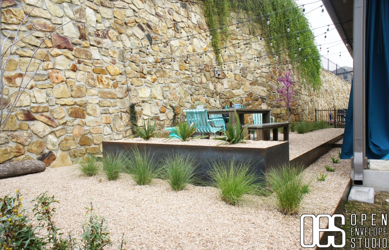 Steel planter and patio with pea gravel; string lights